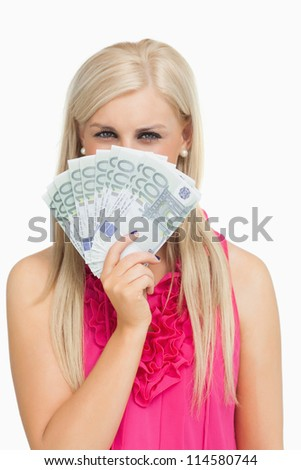 Blonde in pink holding 100 euros banknotes against white background - stock photo