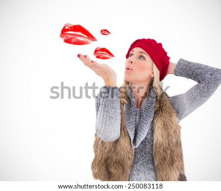 Blonde in winter clothes blowing kiss against white background with vignette - stock photo