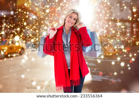 Blonde in winter clothes holding shopping bags against blurry new york street - stock photo