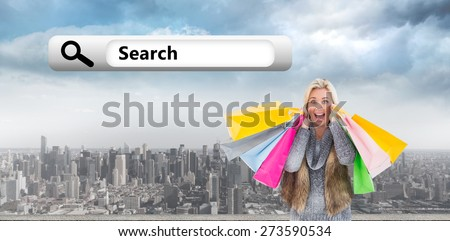 Blonde in winter clothes holding shopping bags against clouds over city - stock photo