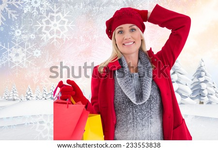 Blonde in winter clothes holding shopping bags against snowy landscape with fir trees - stock photo