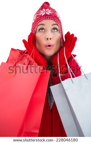 Blonde in winter clothes holding shopping bags on white background
