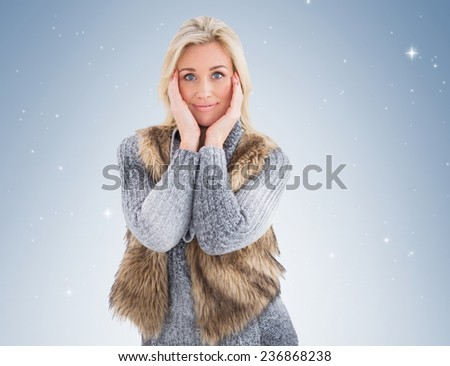Blonde in winter clothes smiling at camera on vignette background - stock photo