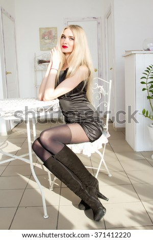 blonde is sitting at a coffee table