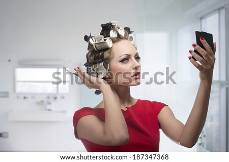 Blonde lady taking care of her style and checking that in the little mirror. Applying make-up with brush and styling her hair with curlers, wearing fashion red dress   - stock photo
