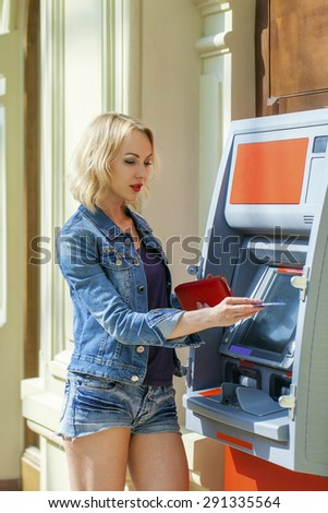Blonde lady using an automated teller machine. Woman withdrawing money or checking account balance