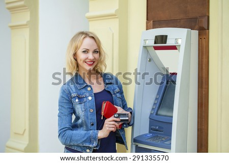 Blonde lady using an automated teller machine. Woman withdrawing money or checking account balance - stock photo