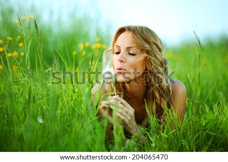 blonde lays and blow on dandelion - stock photo