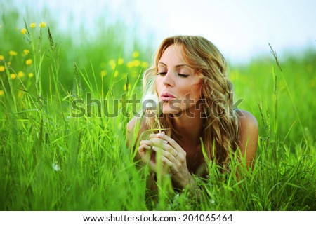 blonde lays and blow on dandelion, saturated colors - stock photo
