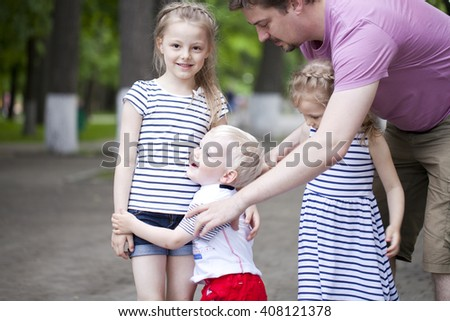 Blonde Little boy and two older cousins sisters, meeting in the summer park - stock photo