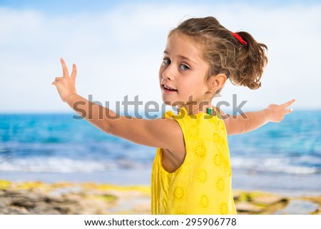 Blonde little girl dancing at the beach