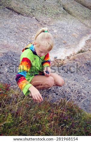 Blonde little girl gathering wild berries   - stock photo