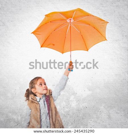 Blonde little girl holding an umbrella - stock photo