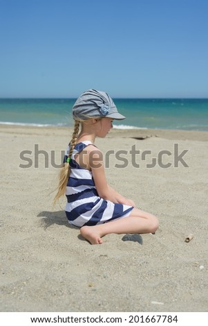Blonde little girl on the beach - stock photo