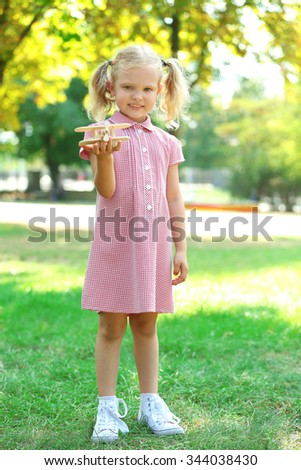 Blonde little girl plays with wooden plane at the park - stock photo