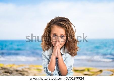 Blonde little girl pleading on unfocused background - stock photo