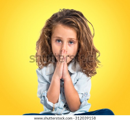 Blonde little girl pleading over colorful backgound - stock photo
