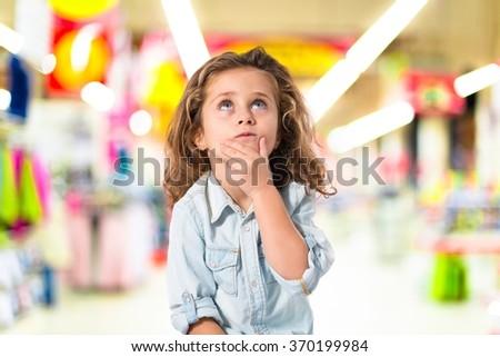 Blonde little girl thinking on unfocused background - stock photo