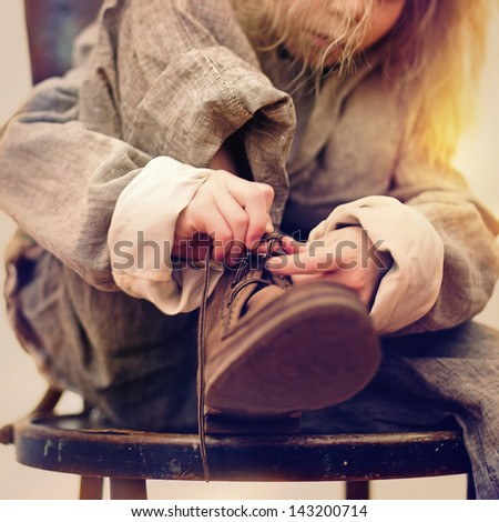 blonde little girl tying shoelaces sitting on a chair - stock photo