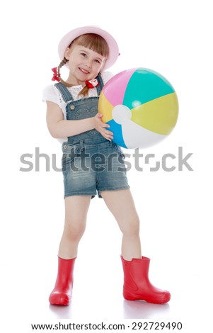 Blonde little girl with a short pigtail with a pink hat , overalls and boots has collected a large bucket of ripe apples - isolated on white background - stock photo