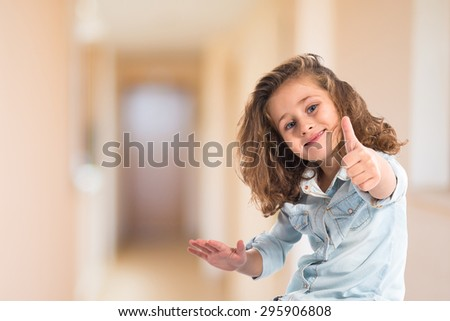 Blonde little girl with thumb up inside house - stock photo
