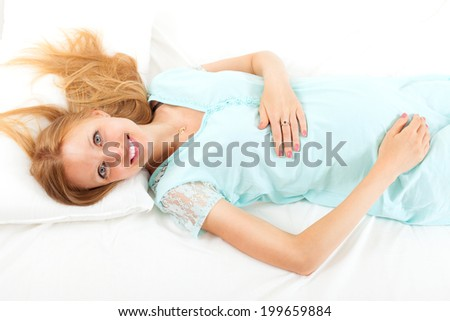 Blonde long-haired pregnancy woman lying on white sheet on her back in bed - stock photo