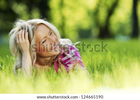 blonde lying on green grass - stock photo