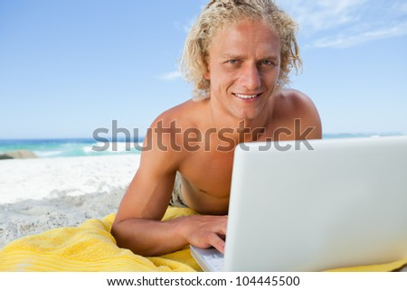 Blonde man lying on the beach while using his laptop and showing a great smile