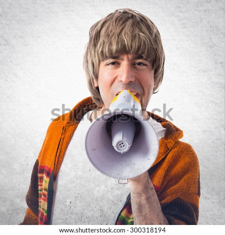 Blonde man shouting by megaphone over grey background