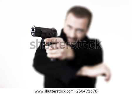 Blonde man with facial hair, aiming with a gun. - stock photo