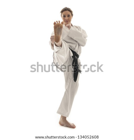 Blonde martial arts girl in kimono exercising karate. Studio isolated portrait.