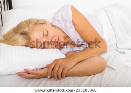 Blonde mature woman sleeping on white pillow in bed at home  - stock photo