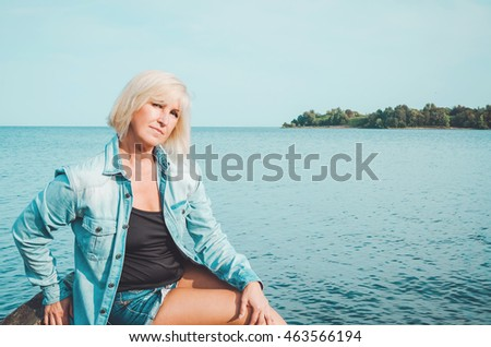 Blonde middle age woman in jeans shirt, sitting on a beach with blue sky background, copy space. Portrait of attractive female have a weekend by the sea. Summer sunny holiday concept.