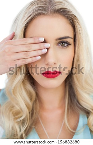 Blonde model in blue dress looking at camera with one eye and hiding the other with her hand on white background - stock photo