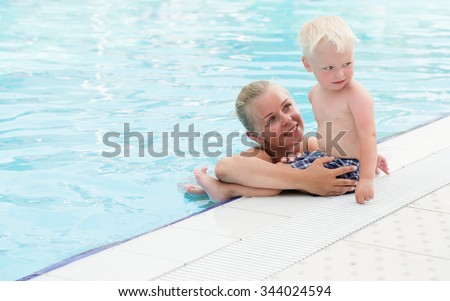 Blonde mother and son have fun by a swimming pool - stock photo