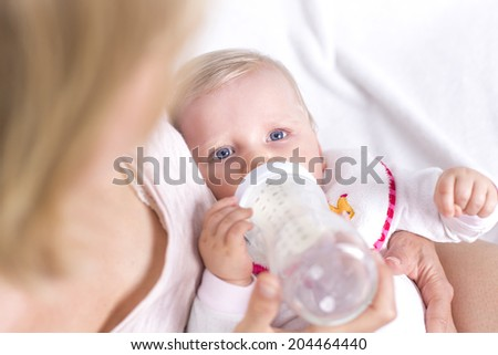 Blonde mother feeding her adorable daughter on the couch - stock photo