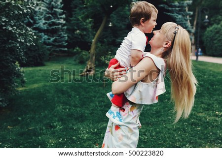 Blonde mother whirls with her little son in red trousers