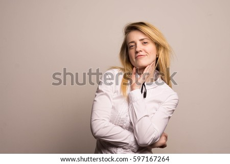 Blonde on a light background beautiful face smiling female student in a white shirt