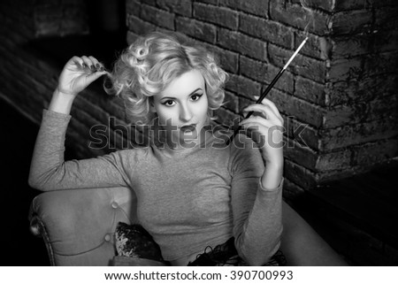 Blonde on a sofa with a cigarette on the background of brick wall