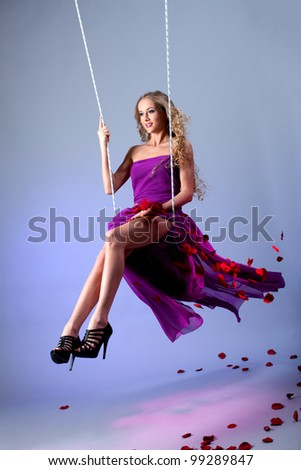 Blonde on a swing with flying rose petals