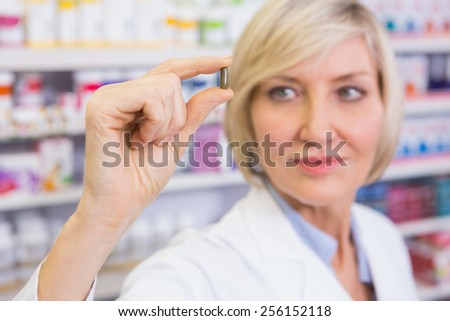 Blonde pharmacist in lab coats showing pill in the pharmacy - stock photo