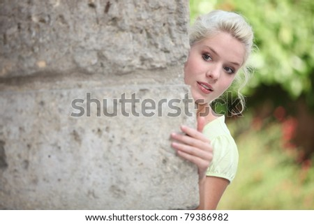 blonde playing hide-and-seek - stock photo