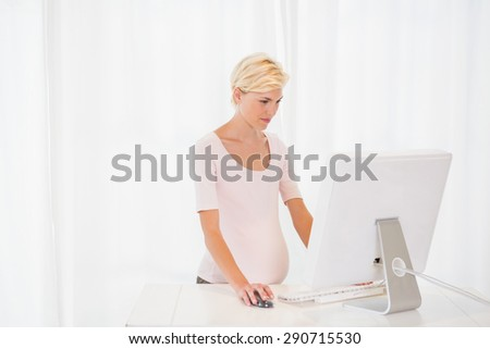 Blonde pregnant using computer in the office - stock photo