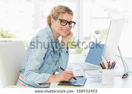 Blonde pretty designer looking at the camera using digitizer in creative office