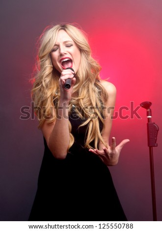 Blonde Rock Star on Stage Singing and Performing - stock photo