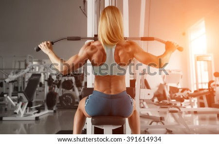 Blonde sexy fitness woman in sport wear with perfect body in the gym posing before training set. Attractive fitness woman, trained female body. Fitness woman in the gym. Bodybuilder woman in the gym. - stock photo
