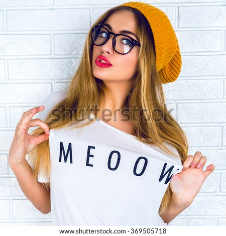 Blonde sexy girl posing near brick wall, happy mood, sensual beauty face, funny shirt, hipster glasses and hat. - stock photo