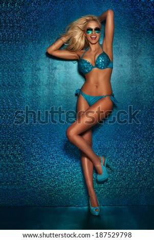 Blonde sexy smiling woman posing in swimsuit and sunglasses. Blue photo. - stock photo