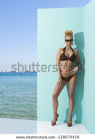 blonde sexy woman in bikini with blonde hair, heels and sunglasses posing near wall. Blue sky, sea and some boats on the background - stock photo