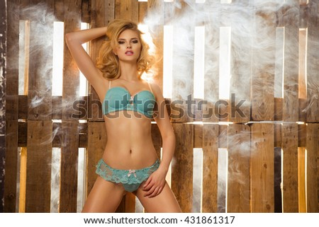 Blonde sexy woman in lingerie stay near wooden pallets